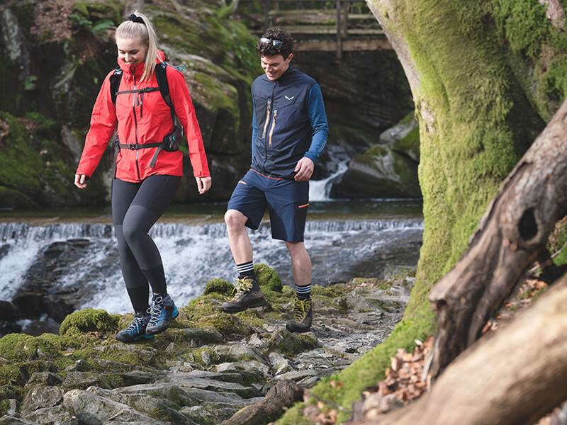 2 walkers walking over rough terrain in boots