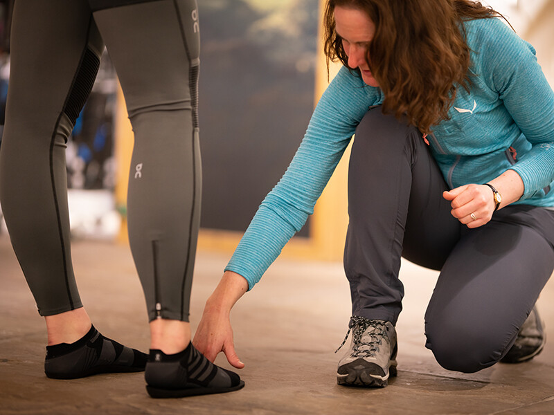 Shop expert checking feet against insole