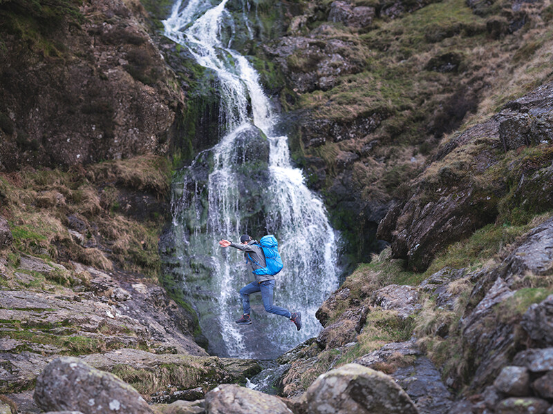 Hiker jumping over stream at bottom of waterfall