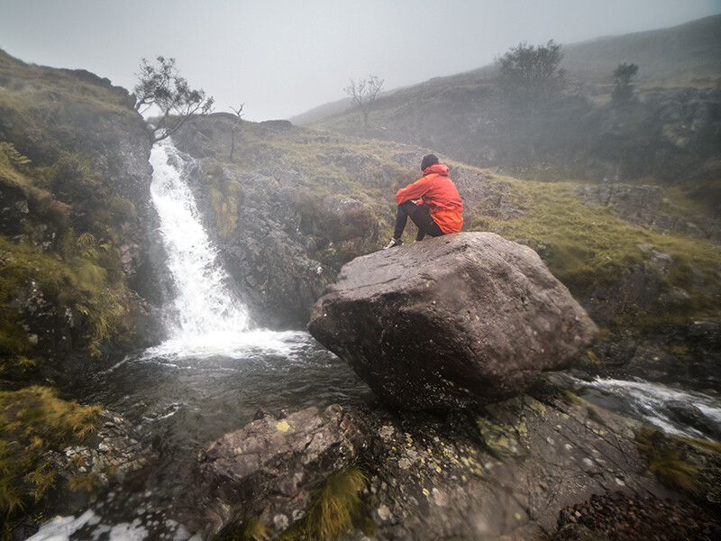 Runner sitting on rock looking at waterfall